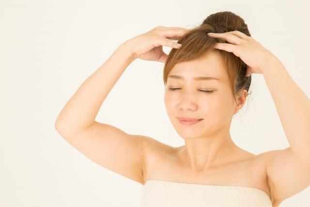 頭皮をマッサージしながら洗っている女性